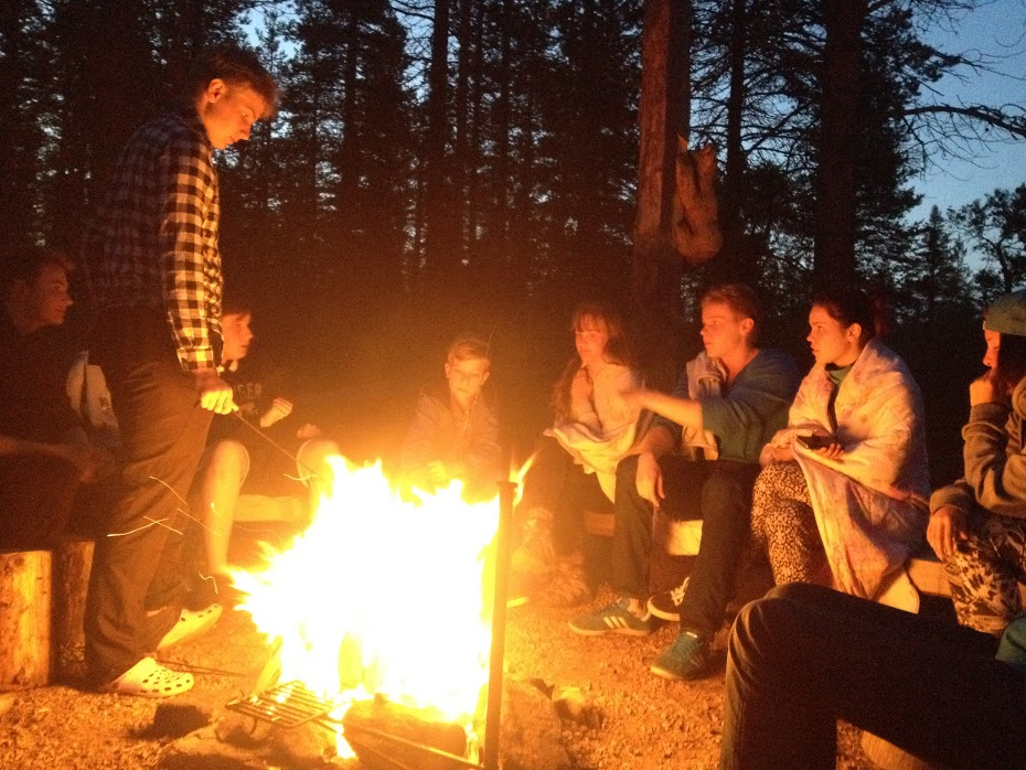 Kuvassa leirituli Lapista, nuotion ympärillä kolmen luokan opiskelijoita.